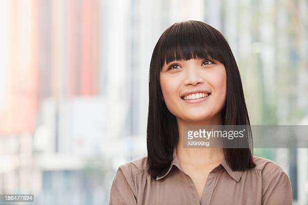 portrait of smiling young woman outdoors in beijing, looking up - bangs hair stock pictures, royalty-free photos & images