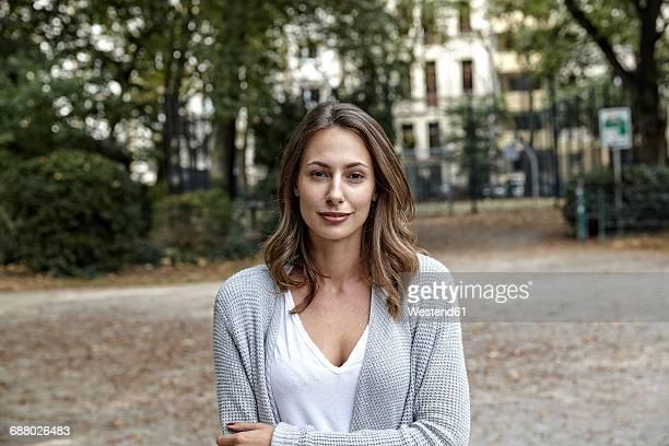 portrait of smiling young woman outdoors - strickjacke stock-fotos und bilder