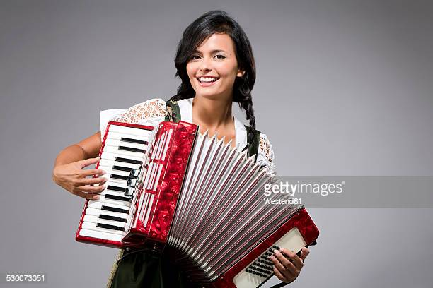 portrait of smiling young woman playing accordion - accordionist stock pictures, royalty-free photos & images