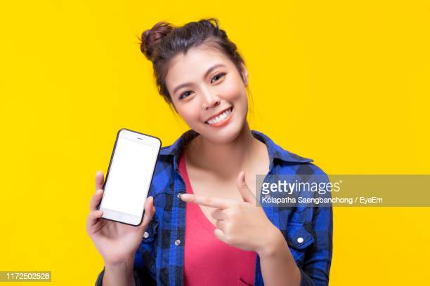 portrait of smiling young woman pointing at smart phone against yellow background - toothy smile stock pictures, royalty-free photos & images
