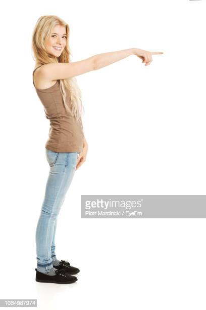 portrait of smiling young woman pointing while standing against white background - human arm stock-fotos und bilder