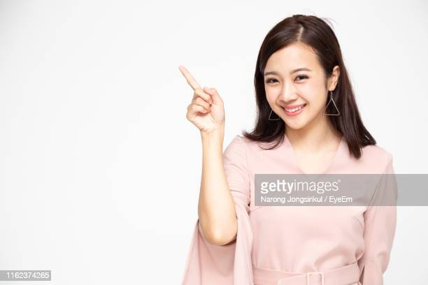 portrait of smiling young woman pointing while standing against white background - zeigen stock-fotos und bilder