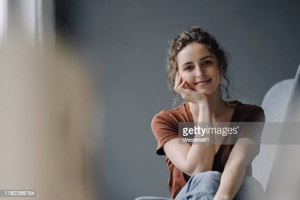 portrait of smiling young woman relaxing at home - variable schärfentiefe stock-fotos und bilder