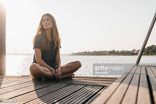 portrait of smiling young woman relaxing on jetty - jetty stock pictures, royalty-free photos & images