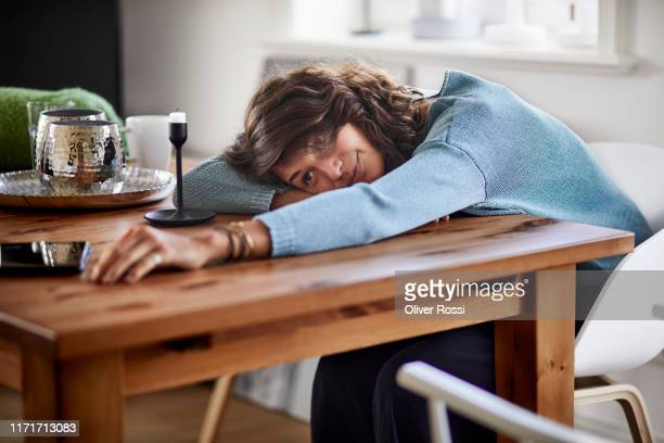 portrait of smiling young woman resting her head on table - image stock-fotos und bilder