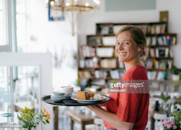 portrait of smiling young woman serving coffee and cake in a cafe - tray stock pictures, royalty-free photos & images