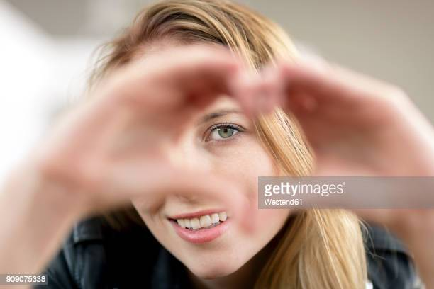 portrait of smiling young woman shaping heart with her hands - gestes photos et images de collection