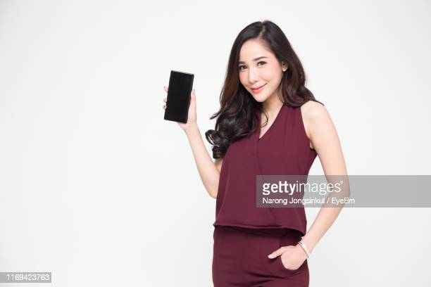 portrait of smiling young woman showing mobile phone against white background - mostrare foto e immagini stock