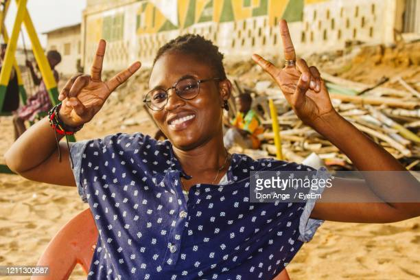portrait of smiling young woman showing peace sign while sitting at beach - femme ivoirienne photos et images de collection