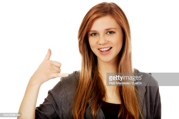 Portrait Of Smiling Young Woman Showing Shaka Sign Against White Background