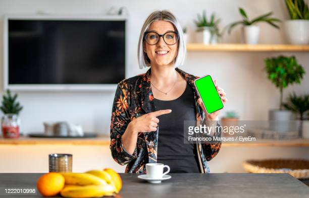 portrait of smiling young woman showing smart phone while sitting at home - mostrare foto e immagini stock