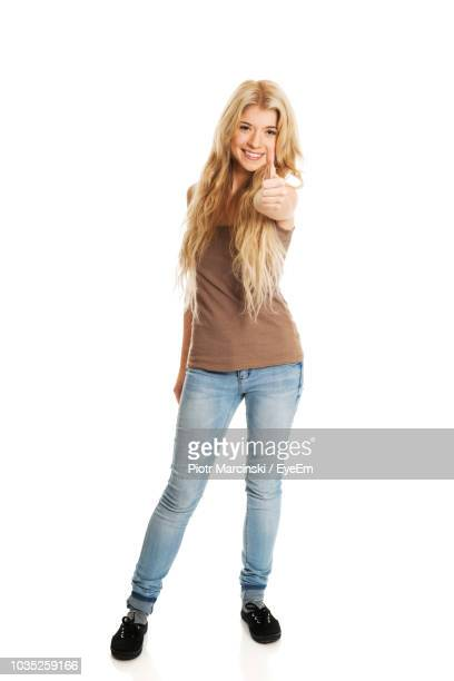 portrait of smiling young woman showing thumbs up while standing against white background - 若い女性一人 ストックフォトと画像