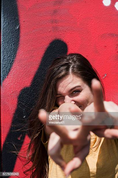 Portrait of smiling young woman showing victory-sign in front of a graffiti