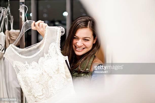 portrait of smiling young woman showing wedding dress - robe de mariée photos et images de collection