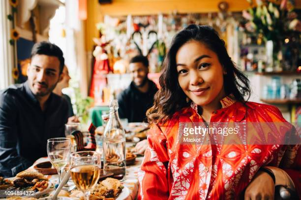 portrait of smiling young woman sitting at table against multi-ethnic friends enjoying brunch in restaurant - selective focus stock pictures, royalty-free photos & images