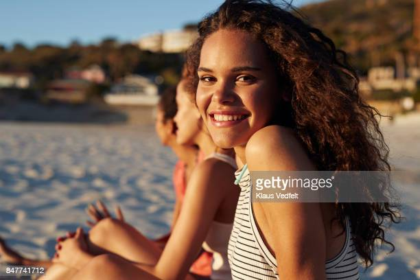portrait of smiling young woman sitting on beach, with friends - girls sunbathing stock pictures, royalty-free photos & images