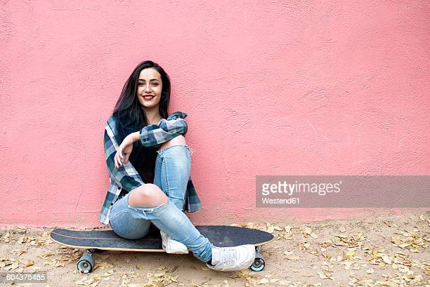 Portrait of smiling young woman sitting on longboard in front of pink wall