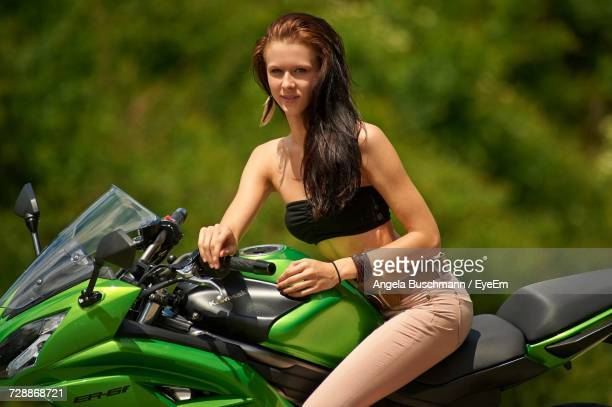 Portrait Of Smiling Young Woman Sitting On Motorcycle