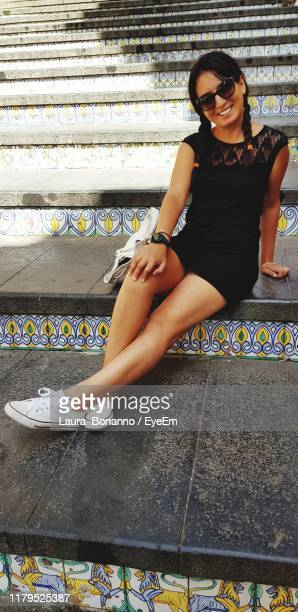 portrait of smiling young woman sitting on staircase - laura belli foto e immagini stock