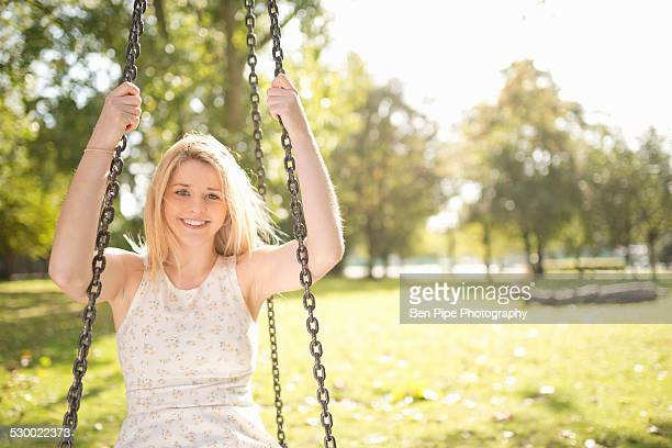portrait of smiling young woman sitting on swing in park - bethnal green stock pictures, royalty-free photos & images