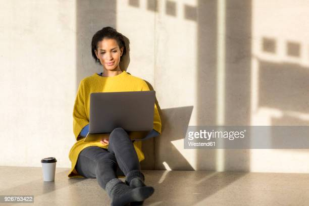 Portrait of smiling young woman sitting on the floor using laptop