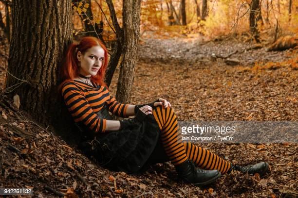 portrait of smiling young woman sitting on tree trunk in forest - forrest compton stock pictures, royalty-free photos & images