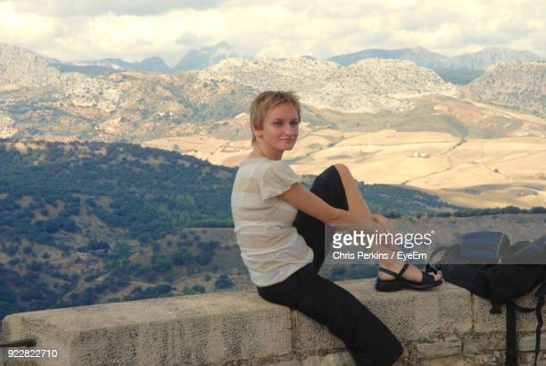 Portrait Of Smiling Young Woman Sitting On Wall At Observation Point