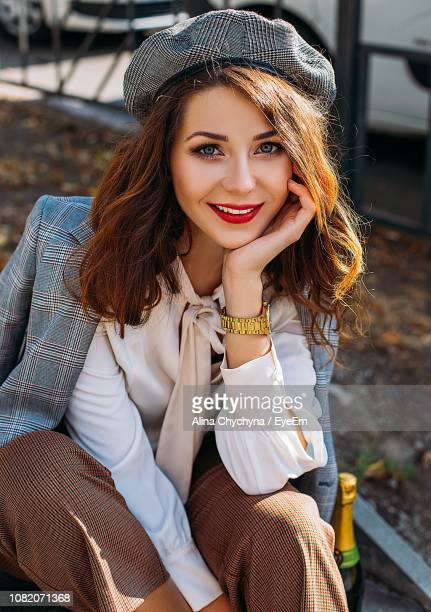 Portrait Of Smiling Young Woman Sitting Outdoors