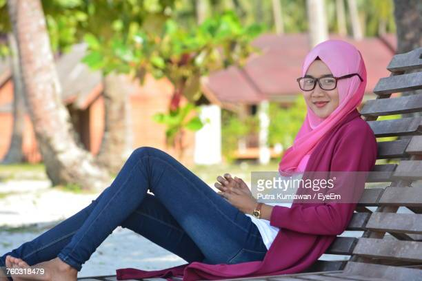 portrait of smiling young woman sitting outdoors - muslim woman beach stock photos and pictures
