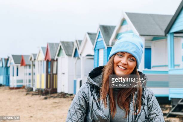 portrait of smiling young woman standing against beach huts - southend on sea stock pictures, royalty-free photos & images