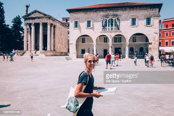 portrait of smiling young woman standing against buildings at town square - イストリア半島 プーラ ストックフォトと画像