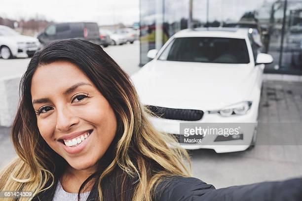 Portrait of smiling young woman standing against car