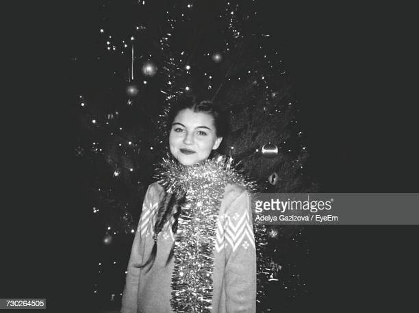 Portrait Of Smiling Young Woman Standing Against Christmas Tree At Night