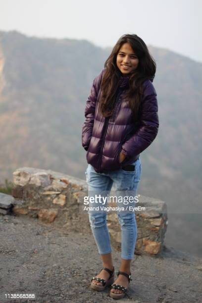 portrait of smiling young woman standing against mountains - beautiful east indian women stock pictures, royalty-free photos & images