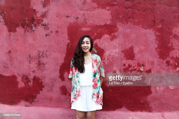 Portrait Of Smiling Young Woman Standing Against Painted Wall