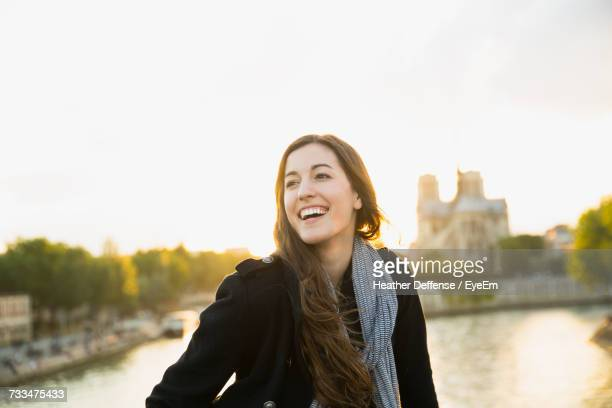 Portrait Of Smiling Young Woman Standing Against River