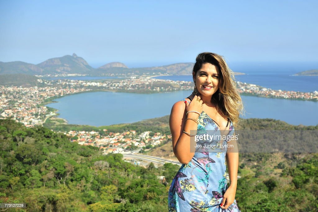 Portrait Of Smiling Young Woman Standing Against Sea : Photo