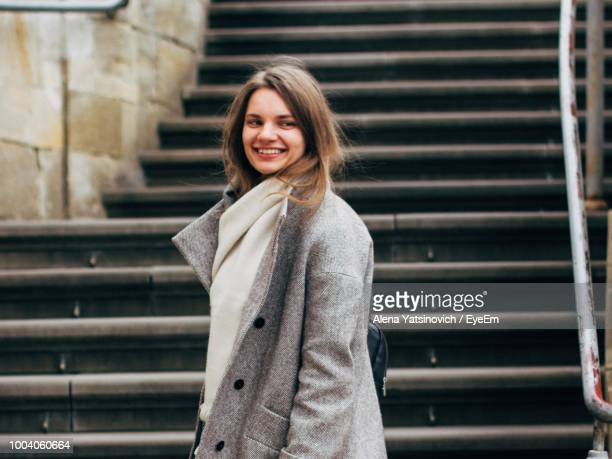 Portrait Of Smiling Young Woman Standing Against Steps