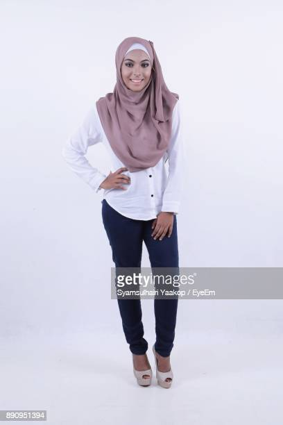 portrait of smiling young woman standing against white background - マレーシア ストックフォトと画像