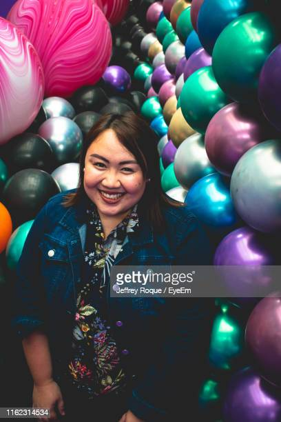 portrait of smiling young woman standing amidst colorful balls - jeffrey roque stock photos and pictures