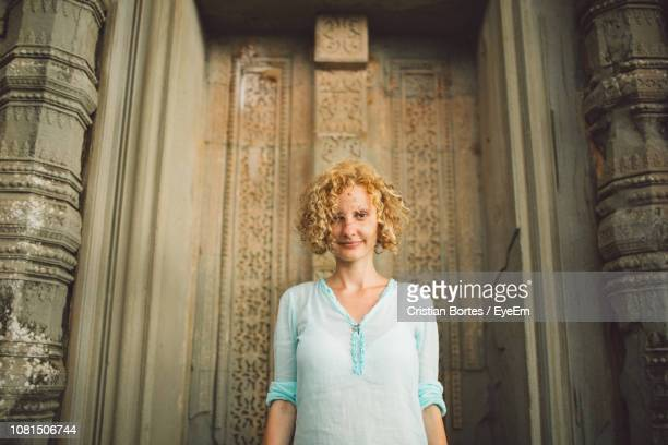 portrait of smiling young woman standing at angkor wat - bortes stock pictures, royalty-free photos & images