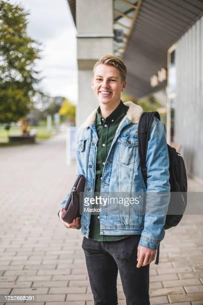portrait of smiling young woman standing at university campus - 20 24 jaar stockfoto's en -beelden