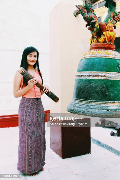 portrait of smiling young woman standing by bell at temple - ko ko htike aung stock pictures, royalty-free photos & images
