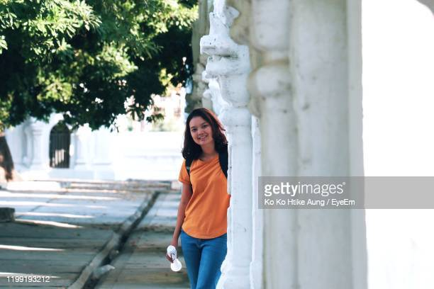 portrait of smiling young woman standing by building - ko ko htike aung stock pictures, royalty-free photos & images