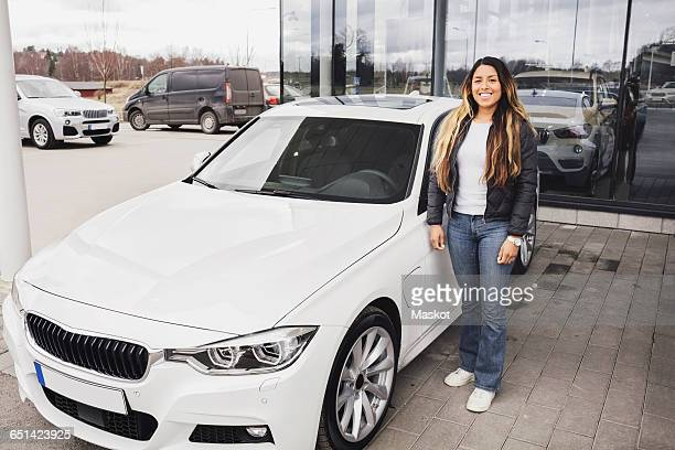 Portrait of smiling young woman standing by car against showroom