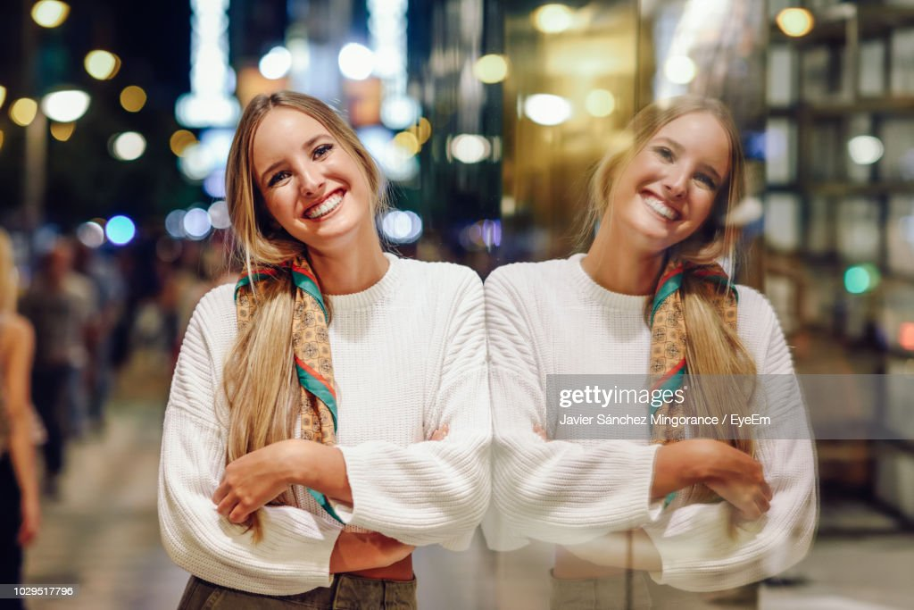 Portrait Of Smiling Young Woman Standing By Glass Window At Night : Foto de stock