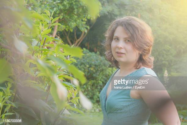 portrait of smiling young woman standing by plants in park - breda stock pictures, royalty-free photos & images