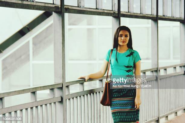 portrait of smiling young woman standing by railing - ko ko htike aung stock pictures, royalty-free photos & images