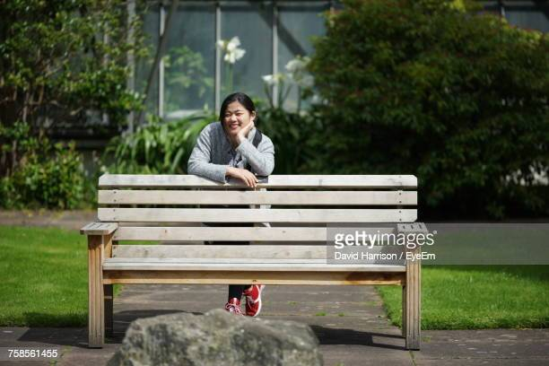 Portrait Of Smiling Young Woman Standing By Wooden Bench At Park