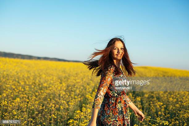 Portrait of smiling young woman standing in a rape field